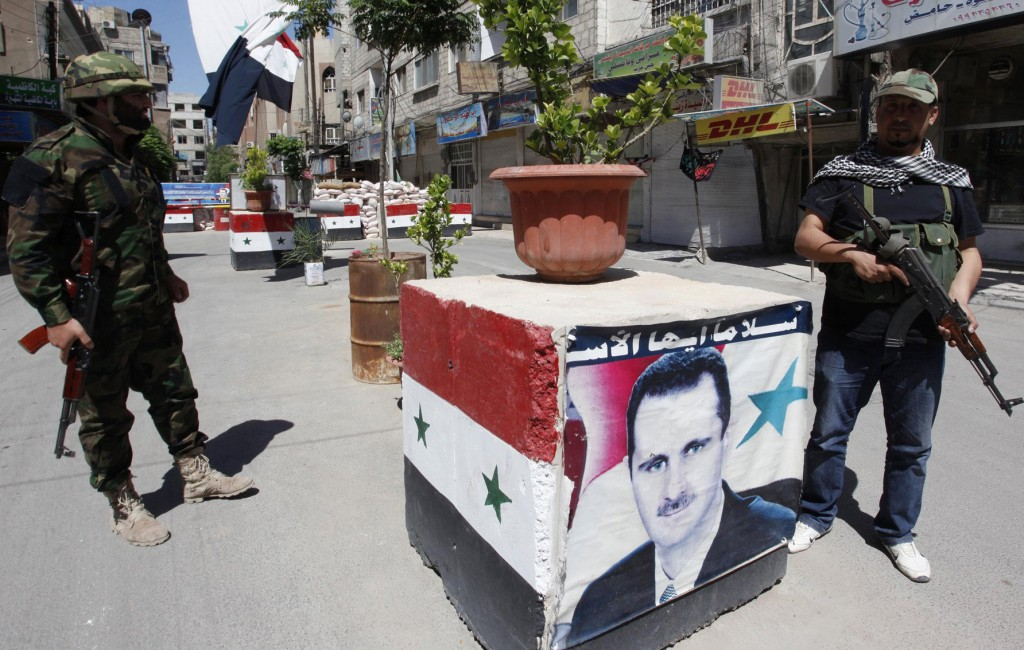 Security personnel loyal to Syria's President Bashar al-Assad stand guard at a checkpoint in Damascus Wednesday. (REUTERS/ Alaa Al-Marjani)