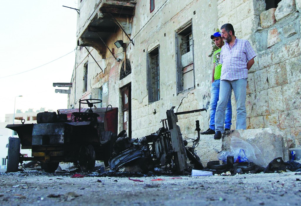 People inspect the damage after overnight clashes in Al-Koubbeh, in Tripoli. (REUTERS/Omar Ibrahim)