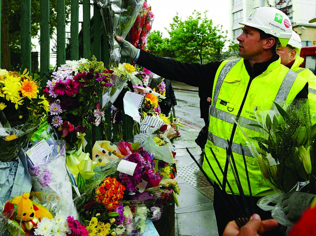 A worker adds flowers to other floral tributes to Drummer Lee Rigby, of the British Army's 2nd Battalion, The Royal Regiment of Fusiliers, at the scene of his killing in Woolwich, southeast London. (REUTERS/ Paul Hackett)