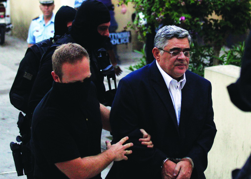 Leader of the extreme far-right Golden Dawn party Nikos Michaloliakos is escorted by anti-terror police at the court , in Athens. (AP Photo/Kostas Tsironis)