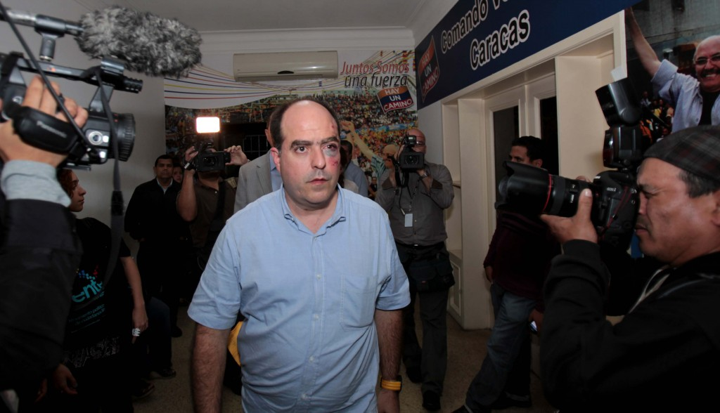 Opposition lawmaker Julio Borges arrives with a bruised face to his political party's headquarters before speaking to the press in Caracas, Venezuela, Tuesday. (AP Photo/Fernando Llano)