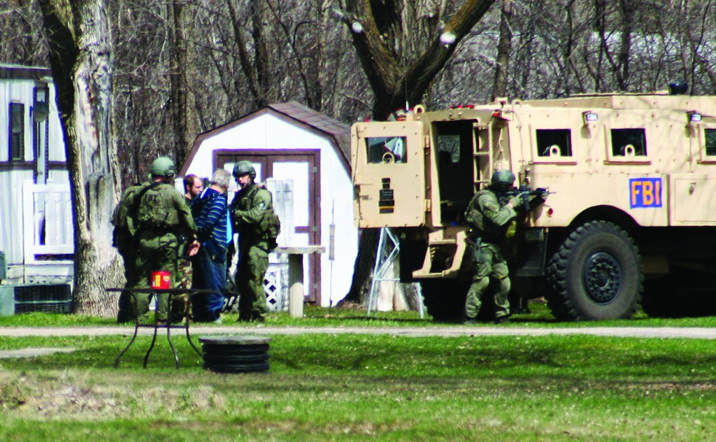 FBI agents with Buford Rogers, back left, and an unidentified man during a raid on a mobile home in Montevideo, Minn. Authorities said Monday that Rogers was arrested Friday and that the agency believes it disrupted a potential terror attack after a search of the home turned up Molotov cocktails, suspected pipe bombs and firearms. (AP Photo/Montevideo American-News, Jeremy Jones)