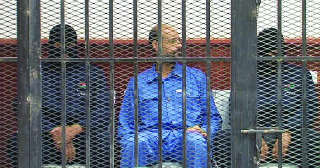 Seif al-Islam Gadhafi, center, inside a defendant's cage in a courtroom in Zintan, Libya, Thursday. (AP Photo/Zintan Media Center)