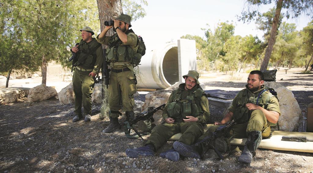 Israeli reserve soldiers watch near the Israel Gaza border on Thursday. (AP Photo/Tsafrir Abayov)