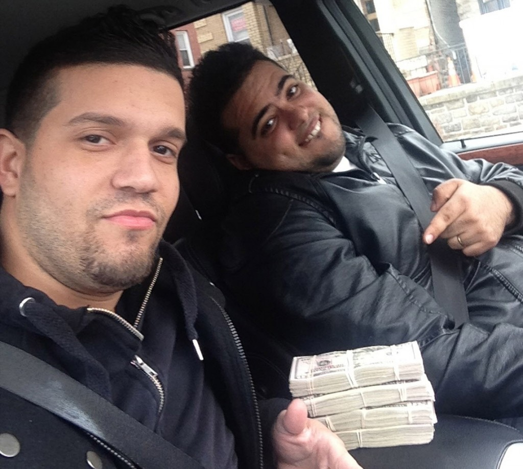Elvis Rafael Rodriguez (L) and Emir Yasser Yeje pose with bundles of cash allegedly stolen using bogus magnetic swipe cards at cash machines throughout New York. (AP Photo/U.S. Attorney's Office)