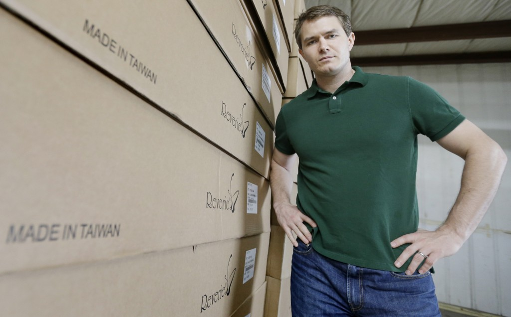 Martin Rawls-Meehan, CEO of Reverie, poses at the company warehouse, next to products made in Taiwan, on May 17, 2013. The company is working to expand manufacturing in the United States.  (AP Photo/David Duprey)