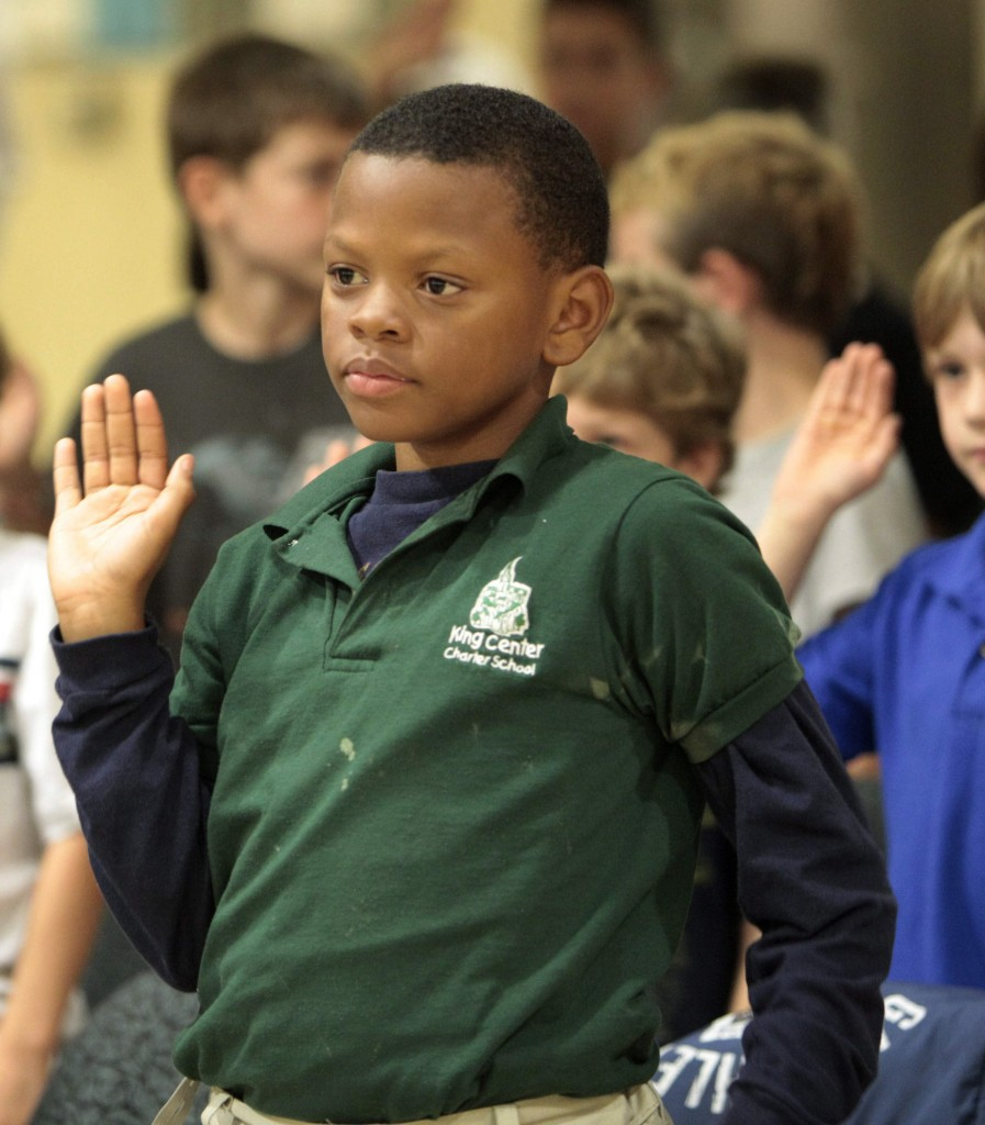 """Fifth-grader in a charter school, Karl Wilson, 10, takes an anti-bully pledge Wednesday during an event to kick off the second annual """"Bullying Stops Here"""" initiative at the Buffalo and Erie County Public Library Central Branch. (AP Photo/The Buffalo News, Derek Gee)"""