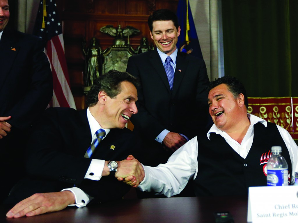 Gov. Andrew Cuomo, left, and Chief Ron LaFrance of the St. Regis Mohawk Tribal Council shake hands after signing an agreement Tuesday in Albany. (AP Photo/Mike Groll)