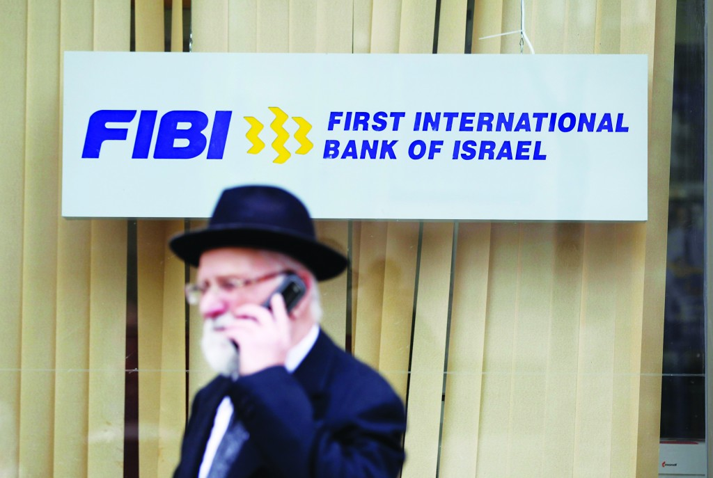 A man speaks on his mobile phone as he walks in front of a First International Bank of Israel branch in Yerushalayim. Israeli conglomerates will offload billions of dollars worth of assets over the next few years to comply with a new law designed to dilute the power of big business. One of those affected by the law is First International Bank, the country's fifth-largest lender. (REUTERS/Baz Ratner)