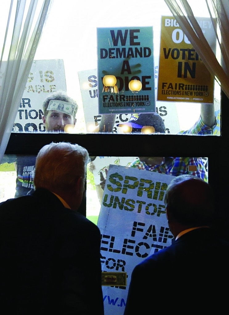 Protesters on Tuesday chant outside the window of a Senate conference room during a hearing highlighting abuses in the public financing of campaigns in New York City. (AP Photo/Mike Groll)