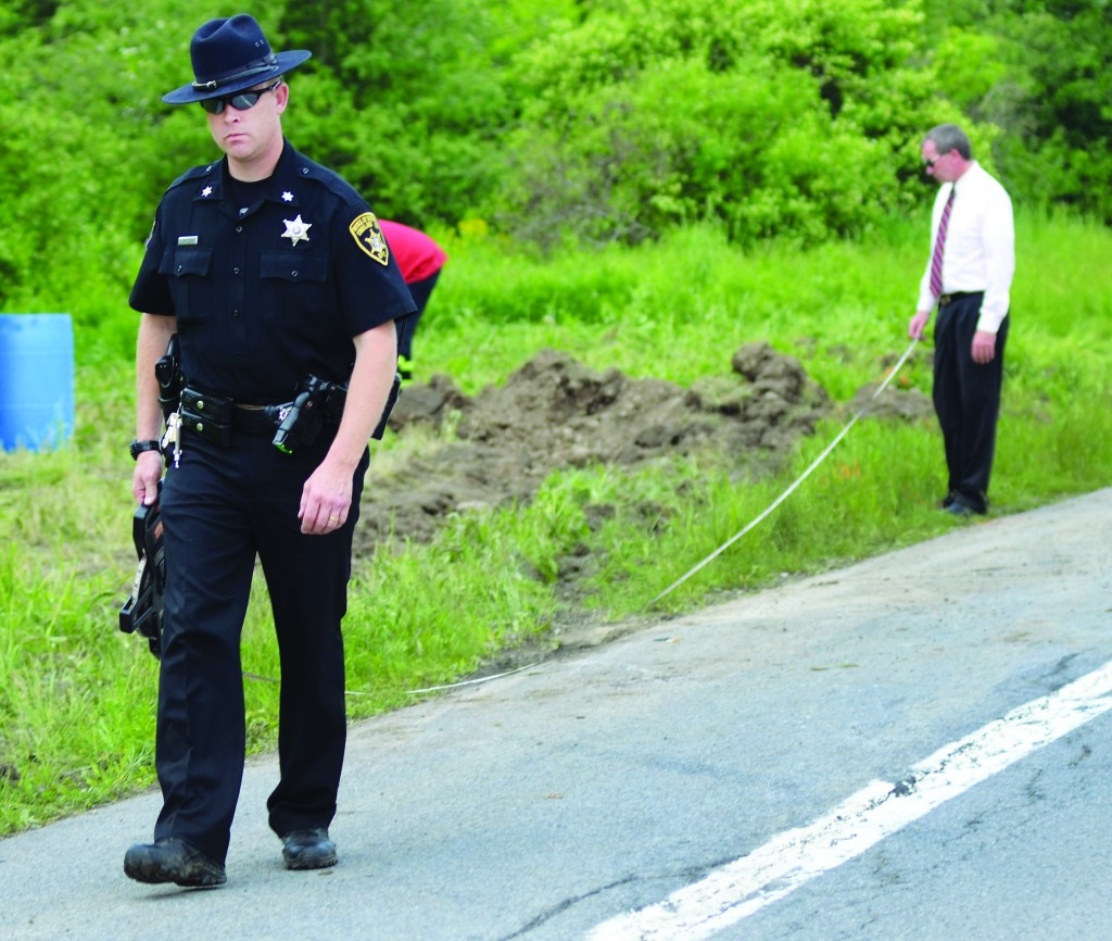 Law enforcement officials at the scene of the fatal car crash in Truxton, N.Y., that killed four children and three adults.(AP Photo/Heather Ainsworth)