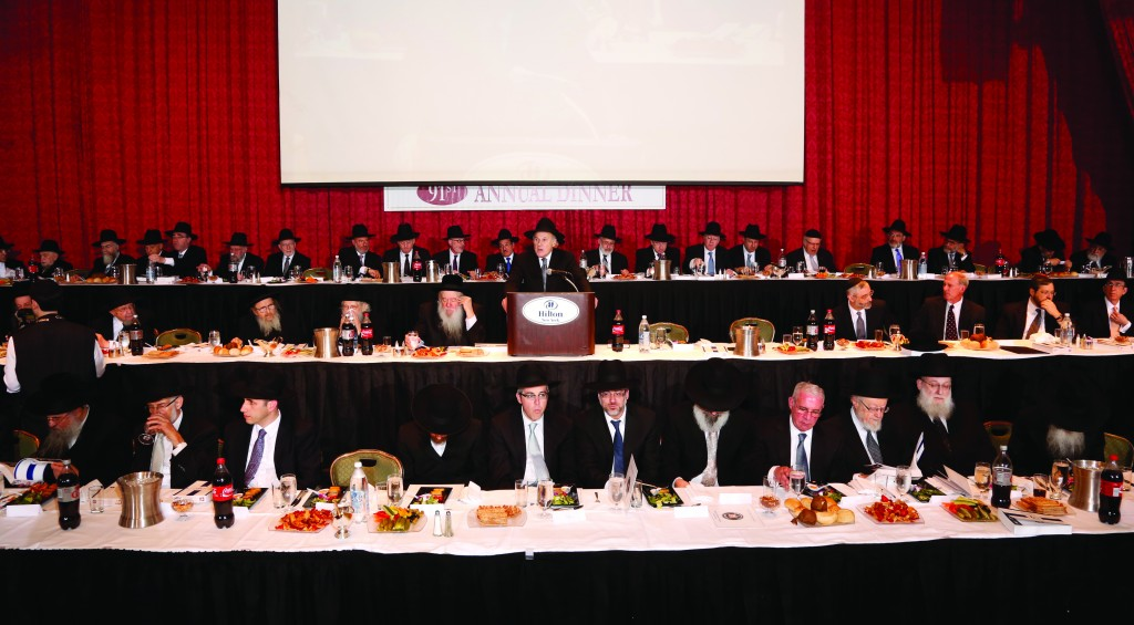 A partial view of the dais at the 91st annual dinner of Agudath Israel of America, last night. Dr. David Diamond, member of the board of trustees of Agudath Israel and chairman of the dinner, is addressing the participants.