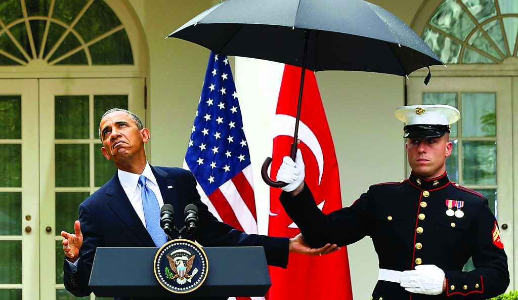 President Barack Obama checks and decides that he no longer needs the umbrella held by a U.S. Marine to protect him from the rain during a joint news conference with Turkish Prime Minister Recep Tayyip Erdogan in the Rose Garden of the White House in Washington, Thursday (REUTERS/Jason Reed)