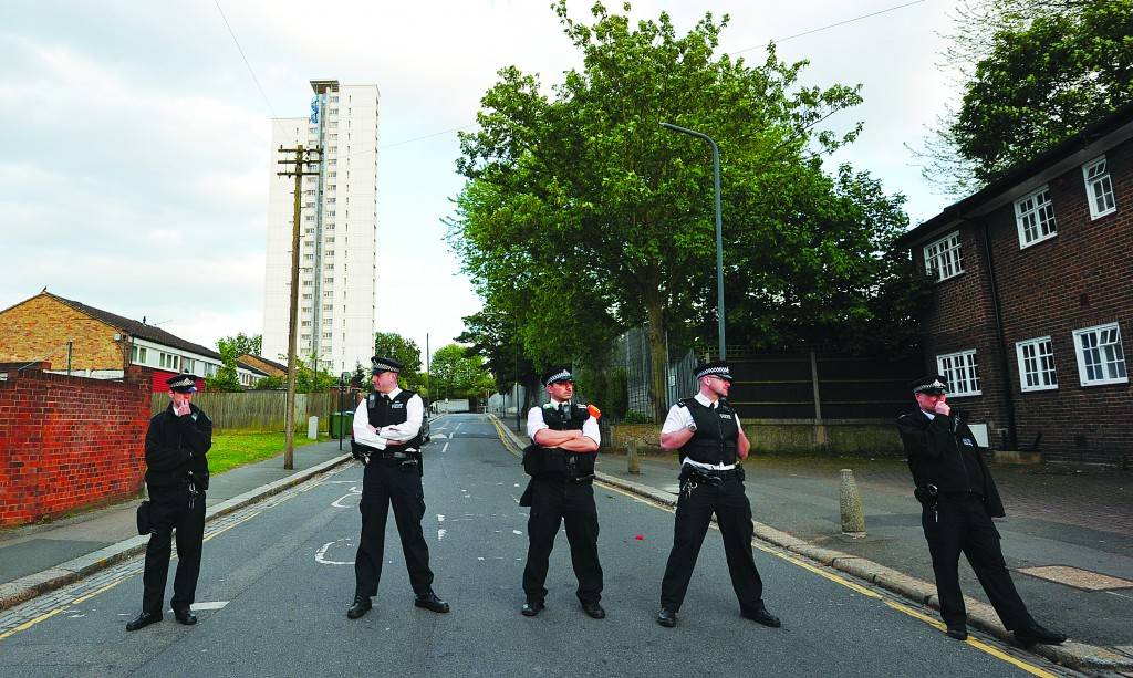 Police officers cordon off a road area in Woolwich, east London, Wednesday, following an incident in which one man was killed and two others seriously injured. (CARL COURT/AFP/Getty Images)