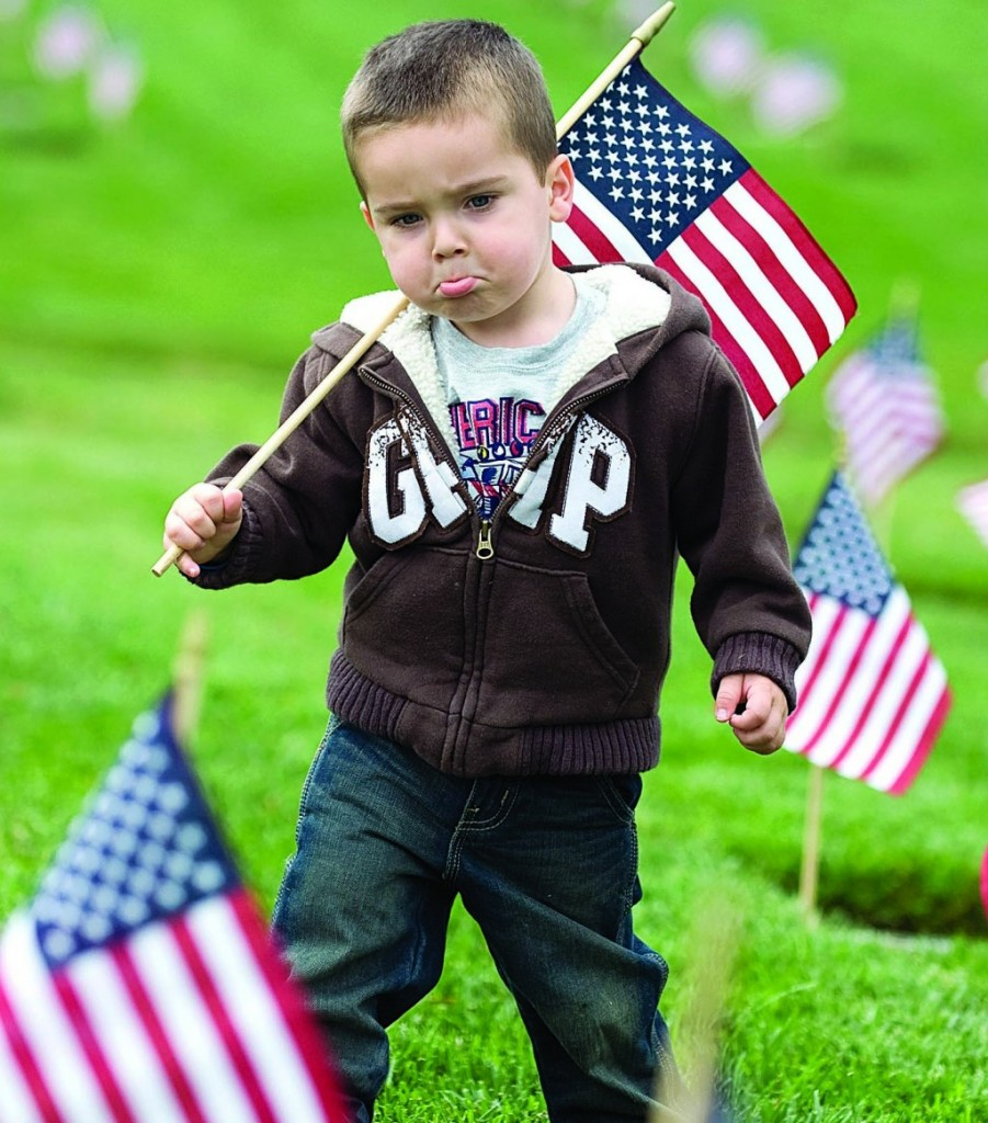Two-year-old Benjamin Pontes helps his mother place flags on veterans' graves at Riverside National Cemetery in Riverside, California, in honor of Memorial Day. The massive flag-placing effort was organized in part by U.S. Air Force veteran and Anaheim police officer Brennan Leininger. (AP Photo/The Orange County Register, Mindy Schaue)r