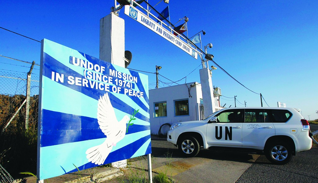 A United Nations armored car drives through a gate at a U.N. base near the Kuneitra border crossing between Israel and Syria, in the Golan Heights Tuesday. Syrian rebels said on Tuesday they detained a group of Filipino U.N. peacekeepers. (REUTERS/Baz Ratner)