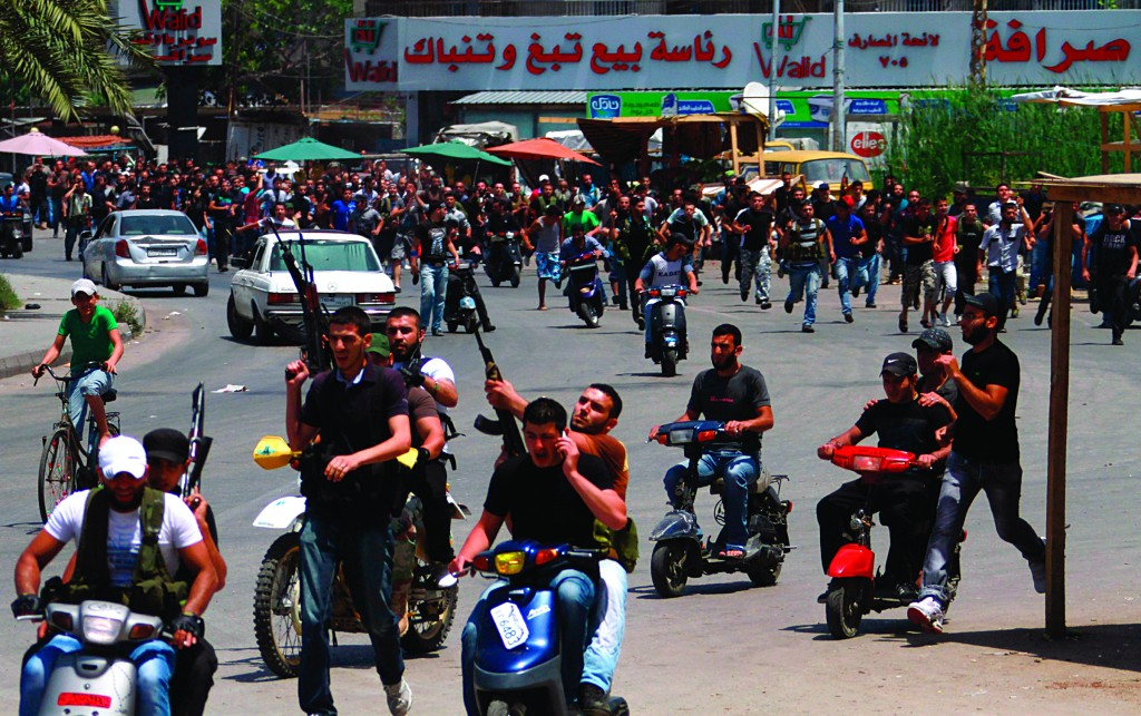 Lebanese Sunni gunmen ride on motorcycles during the funeral of one of their colleagues in Lebanon's northern city of Tripoli Monday. (REUTERS/Omar Ibrahim)