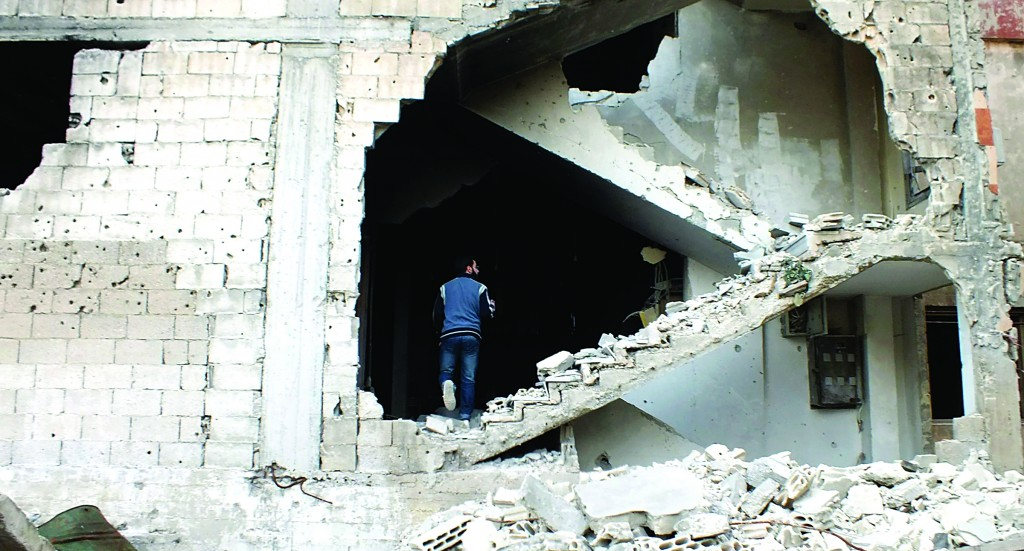 A man is seen on a damaged staircase in Homs Sunday. (REUTERS/Yazen Homsy)