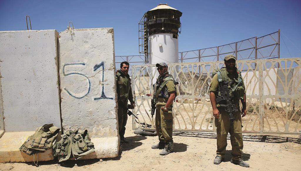 Israeli reserve soldiers stand outside a military post near the Israel Gaza border on Thursday. (AP Photo/Tsafrir Abayov)