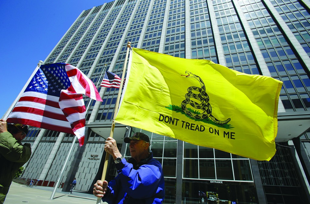 Ty Drake, of Half Moon Bay, Calif., holds a Gadsen flag as he protests during a rally near Internal Revenue Service offices Tuesday, outside the Federal Building in San Francisco. (AP Photo/Ben Margot)