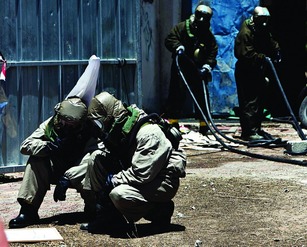 Israeli soldiers, wearing protective gear, take part in a drill simulating a chemical attack in Azur, near Tel Aviv on Tuesday, the second day of an annual home front defense exercise. (REUTERS/Nir Elias)