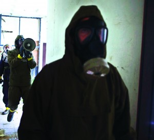 Israeli soldiers, wearing protective gear, search a building for survivors during a drill simulating a chemical attack in Azur, near Tel Aviv on Tuesday, the second day of an annual home front defense exercise.(REUTERS/Nir Elias)