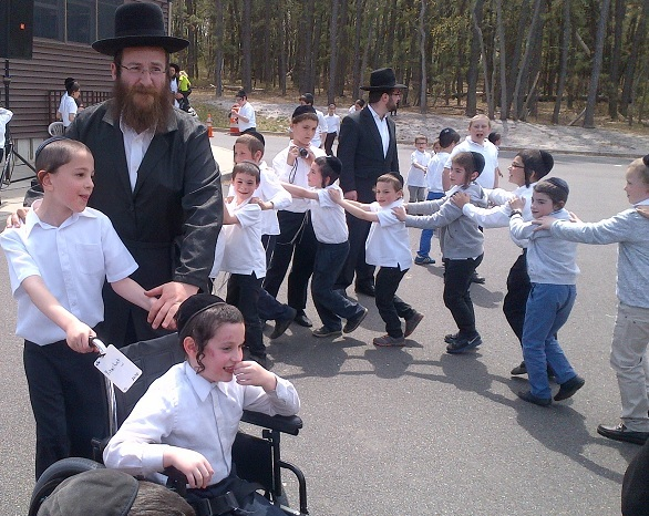 Yitzchok Weisz dancing in his wheelchair around the bonfire at his yeshivah, Toras Emes, last Sunday. (TheLakewoodScoop.com)