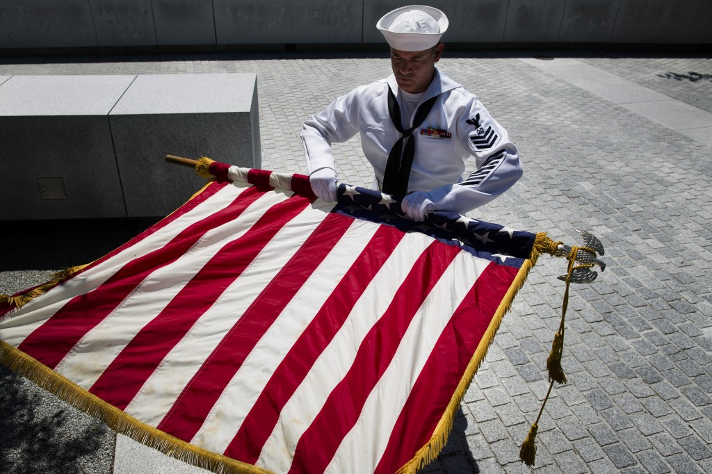 Navy Petty Officer Mark Jones rolls the American flag after a Memorial Day wreath laying at the Franklin D. Roosevelt Four Freedoms Park on Roosevelt Island Monday.(AP Photo/John Minchillo)