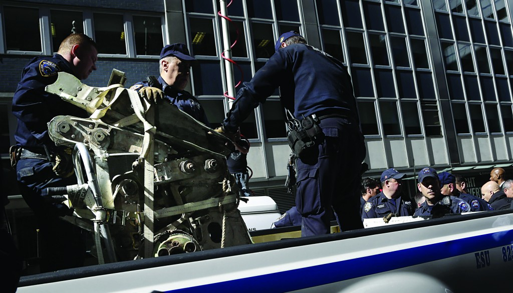 Officials load a suspected 9/11 plane part onto a truck Wednesday. (AP Photo/Seth Wenig)