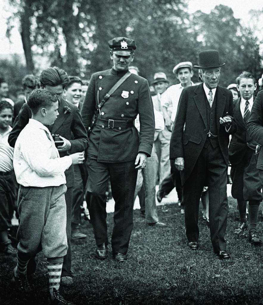 John D. Rockefeller, Sr., (R) the controversial founder of Standard Oil Company and the Rockefeller Foundation, is surrounded by state troopers and youthful admirers during a visit to Lakewood, N.J., on May 14, 1933. (AP Photo)