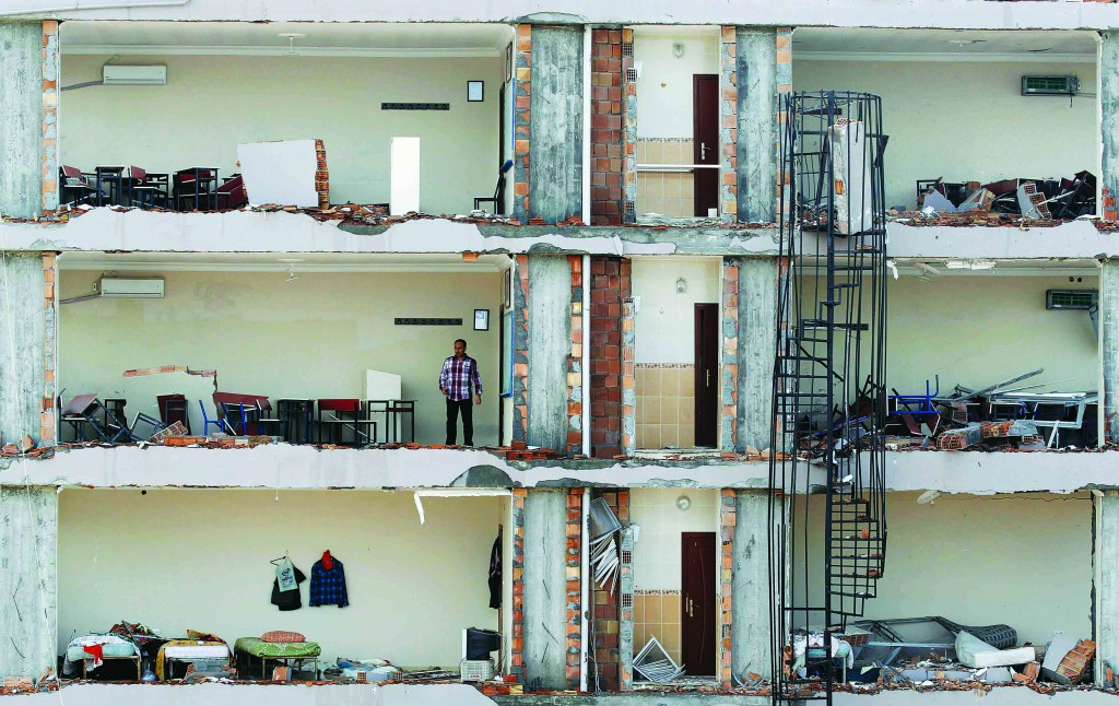A man checks an apartment in a damaged building at the site of a blast in the town of Reyhanli in Hatay province, near the Turkish-Syrian border, Monday. (REUTERS/Umit Bektas)