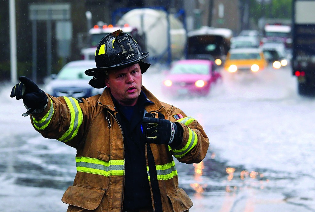 A Jersey City firefighter directs traffic away from a flooded underpass Wednesday as heavy rains flooded streets and stranded some motorists during morning rush hour traffic. (John Moore/Getty Images)