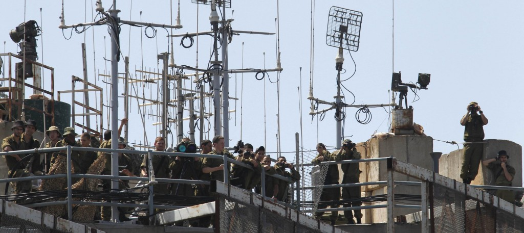 Israeli soldiers monitor the Lebanese-Israeli border as seen from the southern Lebanese village of Houla on Monday. (REUTERS/Ali Hashisho)