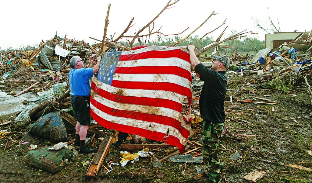 Two men place an American flag on debris Tuesday, May 21, 2013. A monstrous tornado roared through the Oklahoma City suburb of Moore on Monday, flattening entire neighborhoods and destroying an elementary school with a direct blow as children and teachers huddled against winds of up to 200 mph. (AP Photo/Brennan Linsley)
