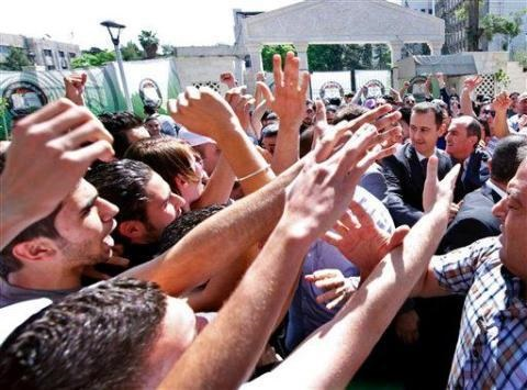 """Syrian president Bashar Assad, right, surrounded by bodyguards as young people wave at him during the inauguration ceremony Saturday of a statue dedicated to """"martyrs"""" from Syrian universities who died in the country's two-year-old uprising and civil war, in Damascus, Syria, Saturday. Assad's second public appearance in a week came as Israeli officials confirmed the country's air force carried out a strike against Syria, saying it targeted a shipment of advanced missiles bound for the Lebanese terrorist group Hezbollah. (AP Photo)"""