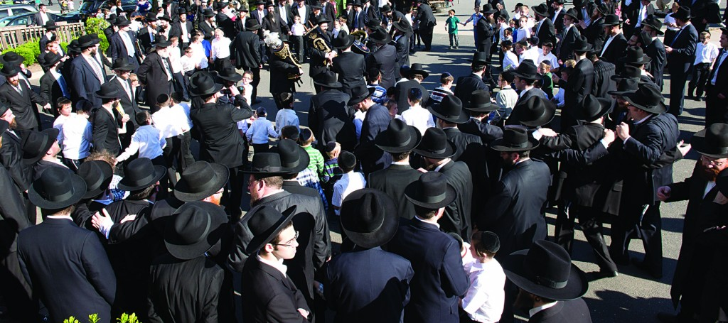"""Hundreds of men and boys danced on Sunday afternoon at a hachnasas sefer Torah in memory of Yosef Meir Berger, z""""l, a 13-year-old bachur who was niftar last year on 13 Adar. The sefer Torah was donated by Yosef Meir's parents, Mr. and Mrs. Ezra Berger, to the Yeshivah Kol Torah on Oak Street, in Lakewood, where Yosef Meir learned. (Hudi Greenberger/Meyer Rosenbaum)"""