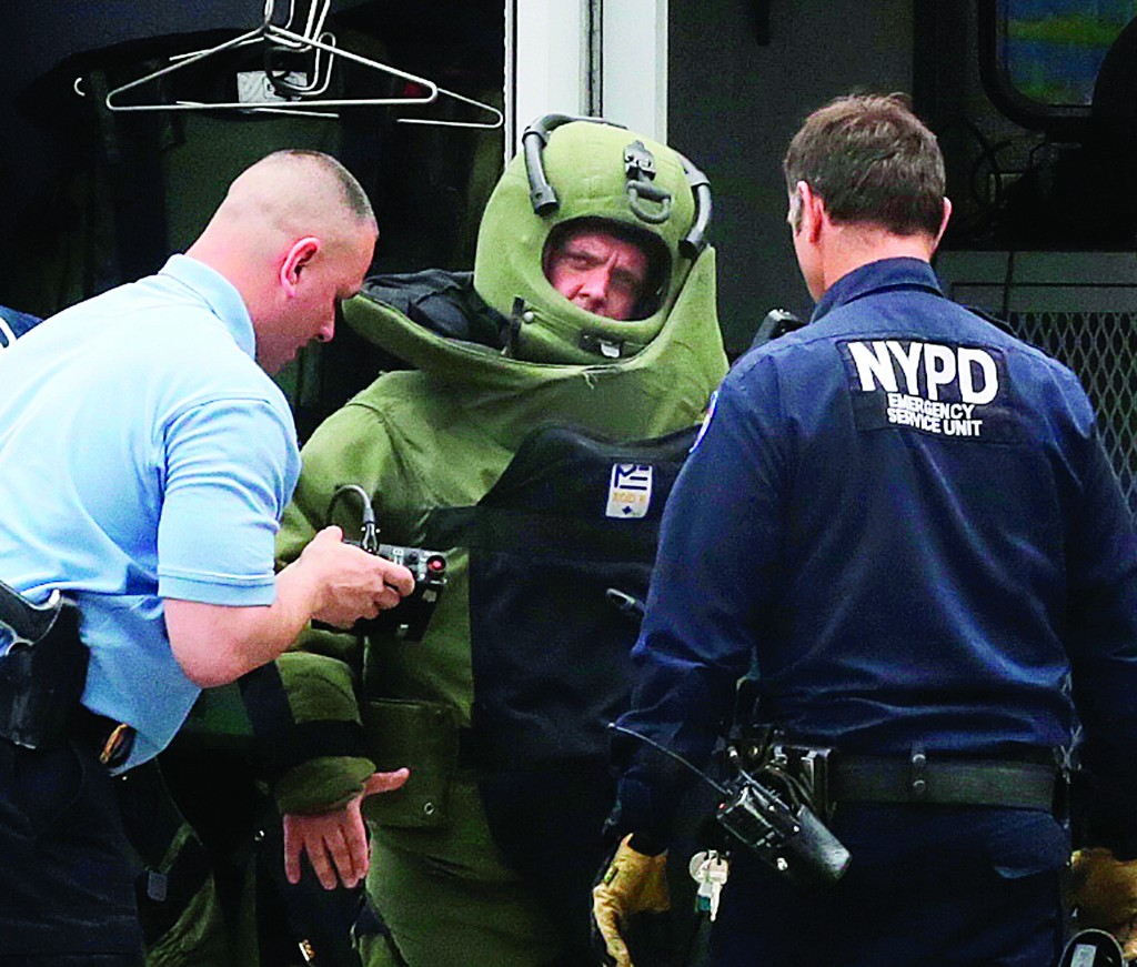 A member of bomb squad gets prepared in a bomb disposal suit to investigate a suspicious package Wednesday in Times Square.(AP Photo/Mark Lennihan)