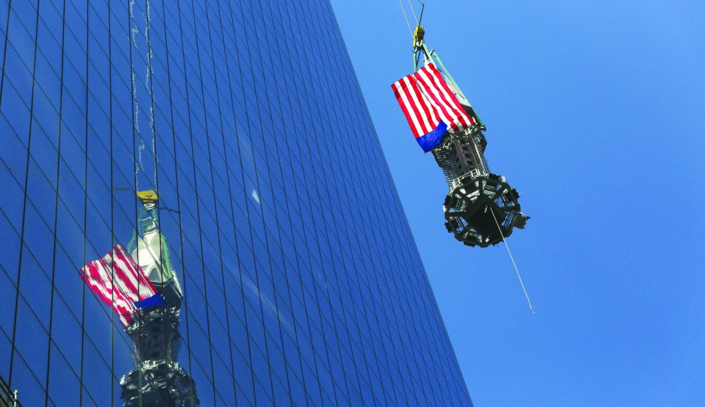 The final piece of the spire is hoisted to the roof of One World Trade Center Thursday. It capped off the tower at 1,776 feet, making it the tallest in the Americas. (AP Photo/Mark Lennihan)