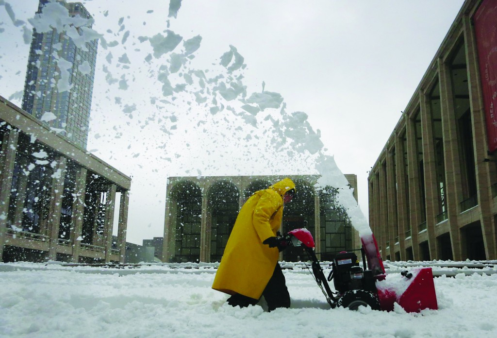 A worker uses a snow blower to clear snow off the steps at Lincoln Center, in Manhattan, February 13, 2014. (REUTERS/Carlo Allegri )