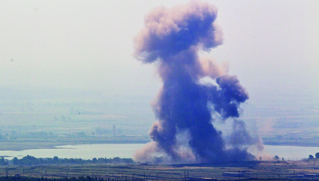 A cloud from an explosion rises near the Syrian village of Al' Rafide at the border with Israel May 7, 2013 in the Golan Heights. Syria admits to firing on an Israeli military vehicle that it falsely claimed crossed the Golan ceasefire line. (Uriel Sinai/Getty Images)