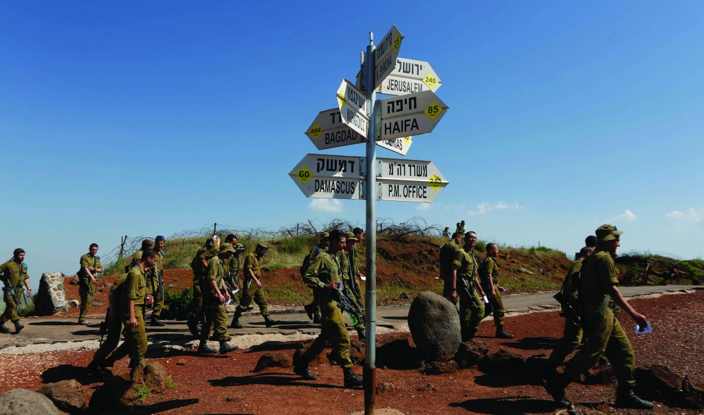 Israeli soldiers walk past signs pointing out distances to different cities at an observation point on Mount Bental in the Golan Heights on May 5. (REUTERS/Baz Ratner)