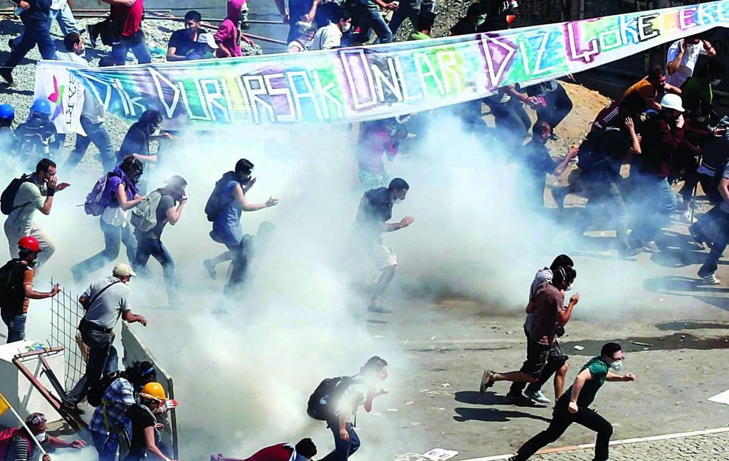 Protesters run as riot police fire teargas during a protest at Taksim Square in Istanbul on Tuesday. (REUTERS/Osman Orsal)