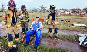 Oklahoma City firefighters check on the status of Gene Tripp as he sits in his rocking chair where his home once stood after being destroyed by a tornado in Oklahoma City, Okla. (AP Photo/The Oklahoman, Chris Landsberger)