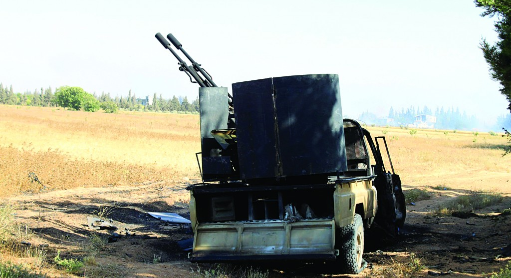 A damaged military vehicle used by the Free Syrian Army sits in a field after heavy fighting against the forces of Syrian President Bashar al-Assad and Lebanon's Hizbullah in the al-Barak area near Qusair. (REUTERS/Rami Bleible)