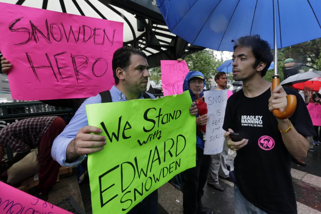 Demonstrators hold signs supporting Edward Snowden in New York's Union Square Park, Monday. (AP Photo/Richard Drew)