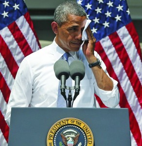 President Barack Obama wipes perspiration from his face as he speaks about climate change, Tuesday, at Georgetown University in Washington. (AP Photo/Charles Dharapak)