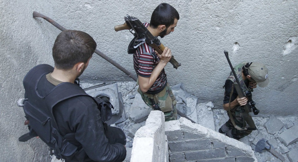 Members of the Free Syrian Army walk down the stairs holding their weapons in Aleppo's Salaheddine district Wednesday. (REUTERS/Hamid Khatib)