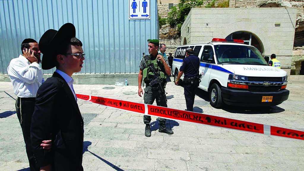 A young man (2nd L) stands near a police cordon at the site of a shooting incident near the Kosel on Friday by a security guard who thought he was a terrorist. (REUTERS/Ammar Awad)