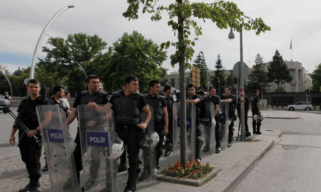 Riot police are stationed on John F. Kennedy Street in front of the U. S. Embassy as several hundreds of protesters march in Ankara, Thursday. (AP Photo/Burhan Ozbilici)
