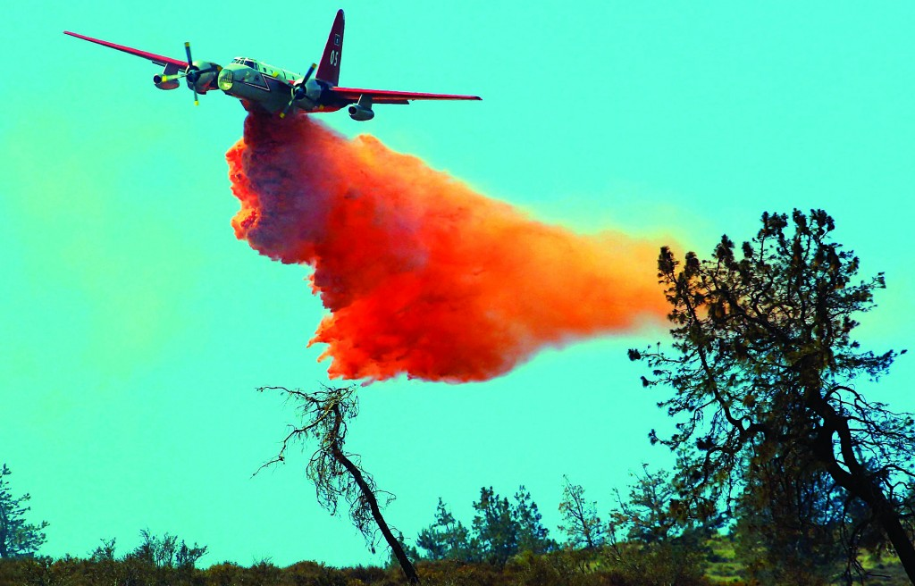 A plane drops water to fight what has been called the Powerhouse fire in the rural community of Lake Hughes in northern Los Angeles County, Calif., Monday. At least six houses have been destroyed by the fire, nine more were damaged, and 2,800 people fled 700 homes in Lake Hughes and Lake Elizabeth, 45 miles northwest of downtown Los Angeles. (AP Photo/Nick Ut)